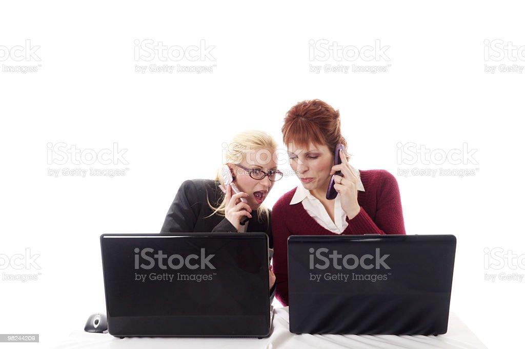 Femmina colleghi reagire a informazioni sul cellulare. foto stock royalty-free