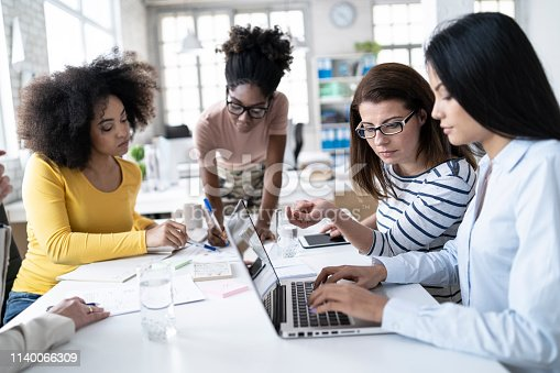 istock Female coworkers working together and using laptop at work 1140066309