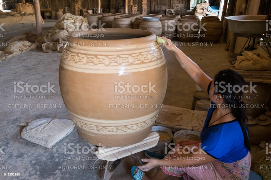 female craftperson uses wet sponge to dub the pattern on big clay pot. stock photo