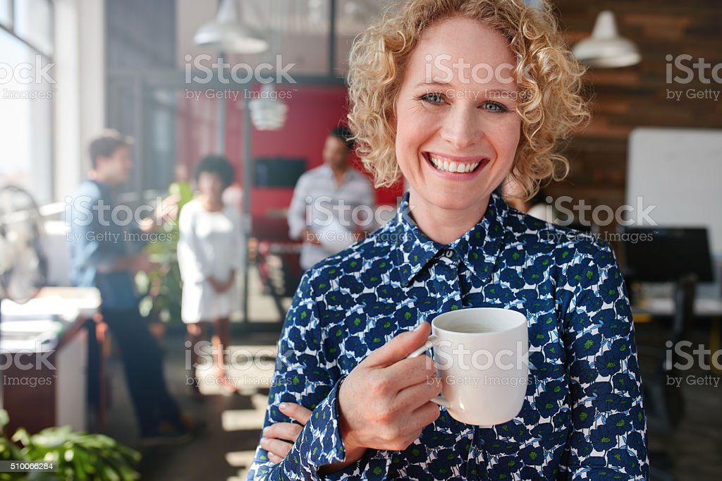 Female creative professional having a coffee in office stock photo