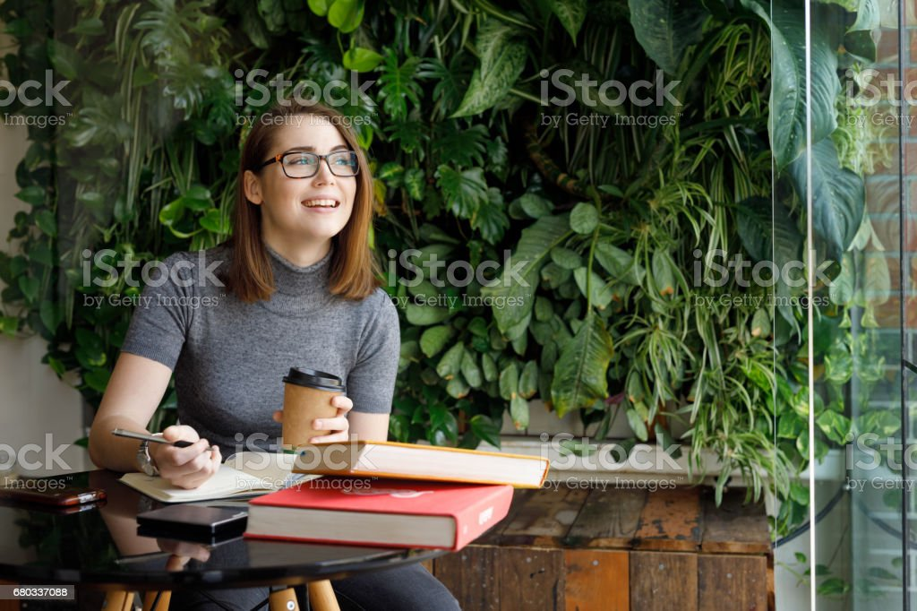 Female Creative smiling while looking out window stock photo