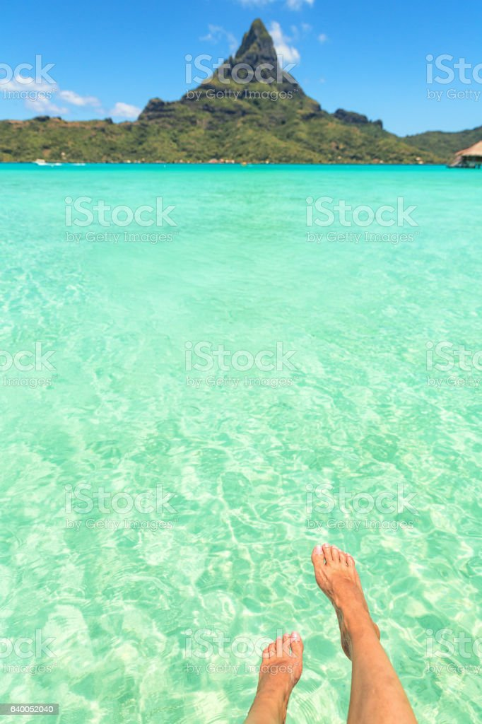 Female crossed legs over tropical blue lagoon and Otemanu mount, stock photo