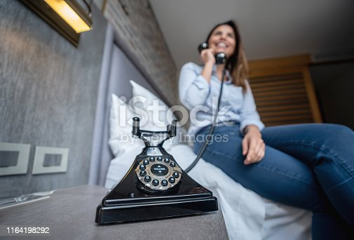 Female customer at a hotel using a vintage phone - Focus on foreground - Low angle view