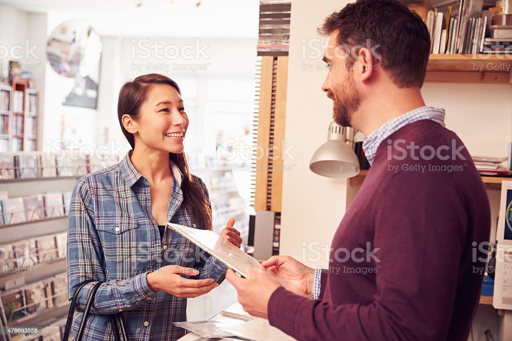 Female customer being served at the counter of record shop stock photo