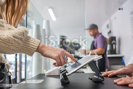 Profile view of a young woman signing the bill on the digital tablet at the register at a local neighborhood coffee shop.