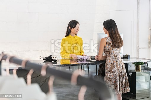 istock Female customer buying garment in modern boutique 1134562269