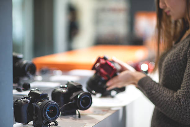 female customer choosing a camera - sale lenses stock photos and pictures