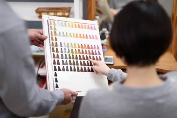 vrouwelijke klant kiezen haar kleur in kapsalon - gekleurd haar stockfoto's en -beelden