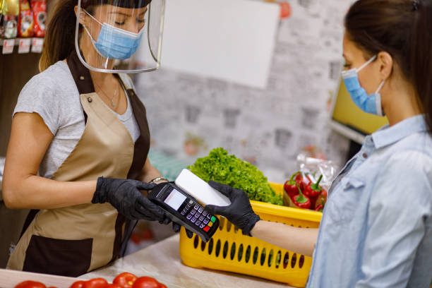 Female customer doing a contactless payment at the supermarket stock photo