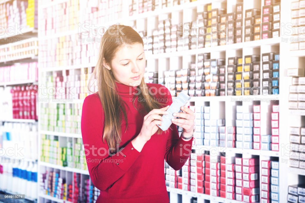 Female customer is choosing hair dye in the hair care shop royalty-free stock photo