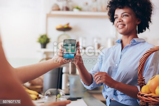 istock Female customer paying for her juice by credit card 537607170