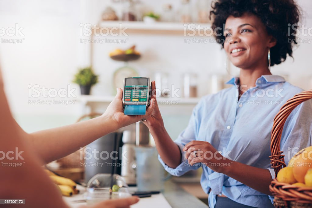 Female customer paying for her juice by credit card stock photo