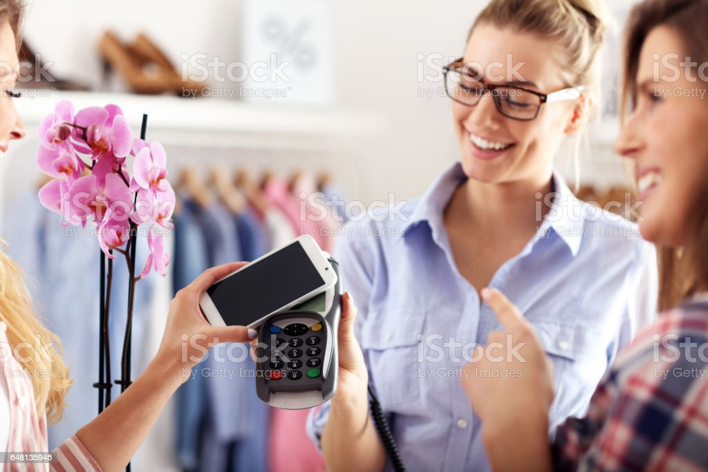 Female customer paying in shop with credit card stock photo