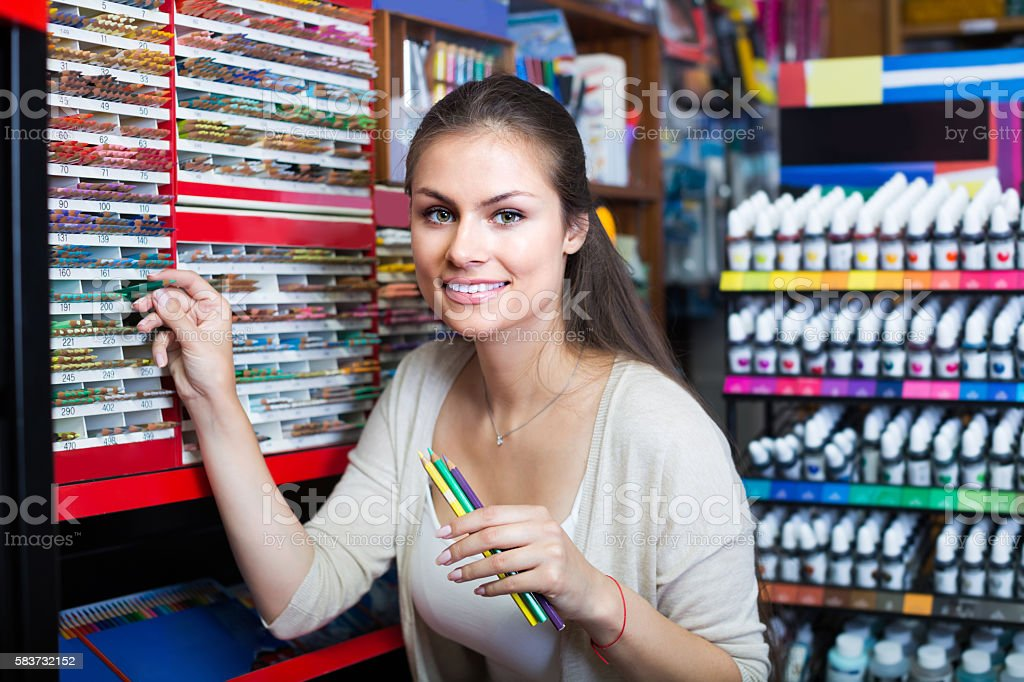 female customer picking pencils in art store stock photo