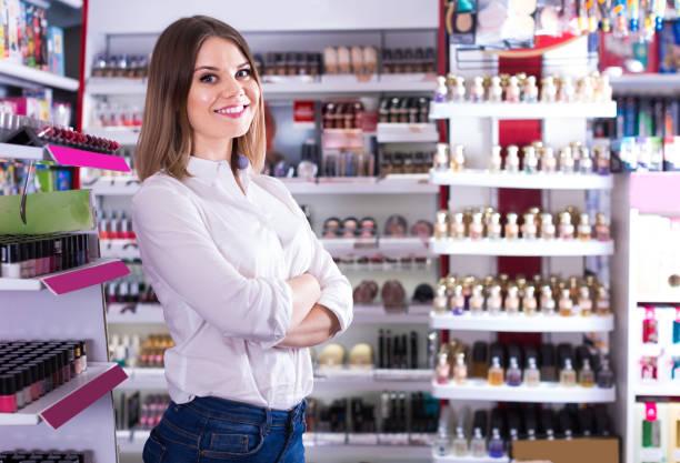 vrouwelijke klant poseren in cosmetica winkel - verkoopster stockfoto's en -beelden