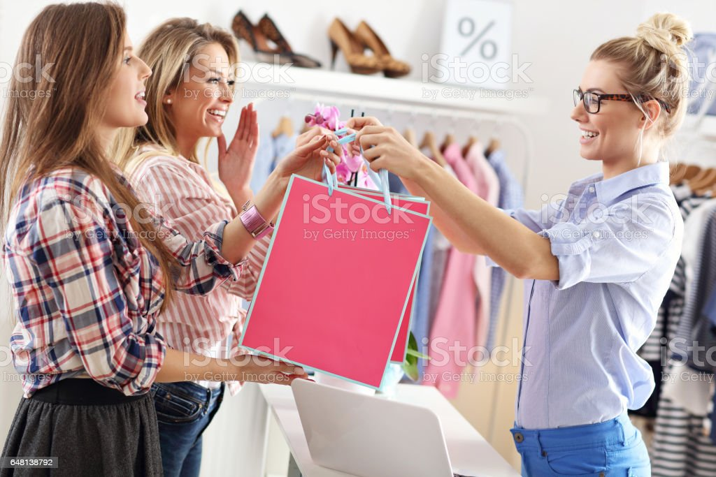 Female customer receiving shopping bags in boutique stock photo