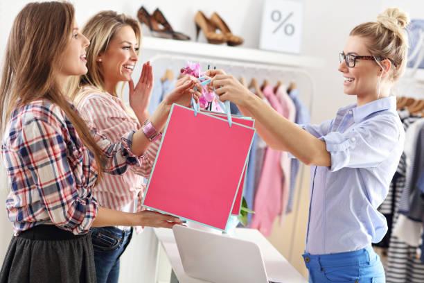 ブティックのショッピング バッグを受ける女性客 - 小売販売員 ストックフォトと画像