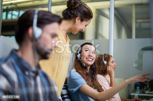 istock Female customer service executive interacting with her colleague at desk 665431186