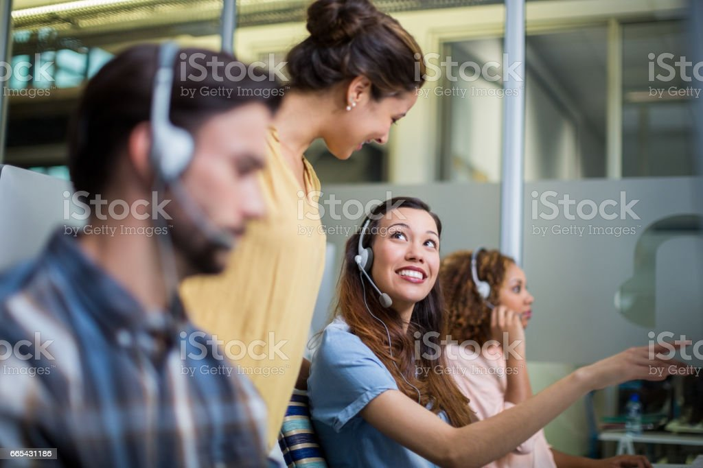 Female customer service executive interacting with her colleague at desk stock photo