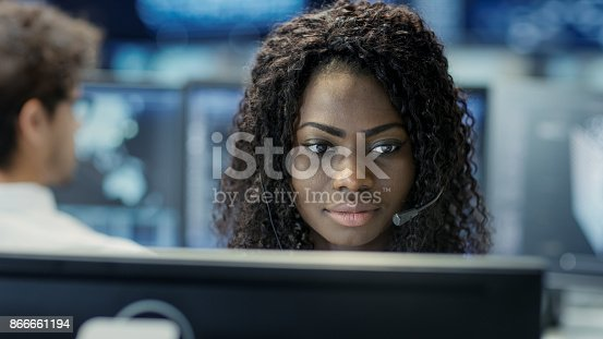 istock Female Customer Service Representative Answer Client's Questions in a Headset. He Works for a Big Technological Company. Office Has Multi-Ethnic Team of Specialists, Displays Show Useful Information. 866661194
