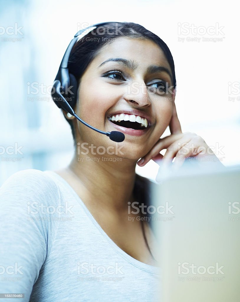 Female customer service representative using headset and laughing royalty-free stock photo