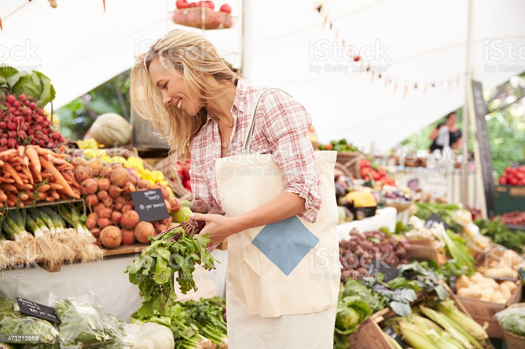 Female Customer Shopping At Farmers Market Stall stock photo