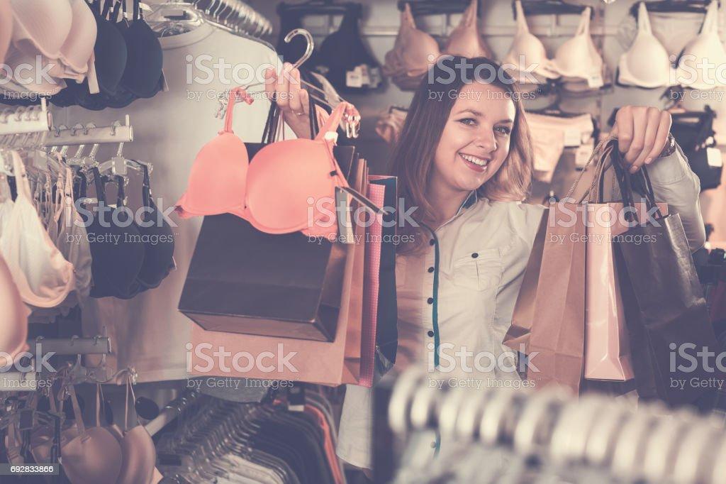 ff1ce2950641 Cliente Mujer Mostrando Sus Compras En La Tienda De Ropa Interior ...
