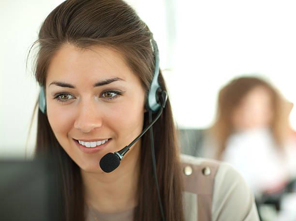 weibliche kunden-support-betreiber mit headset und lächeln - bürorezeption stock-fotos und bilder