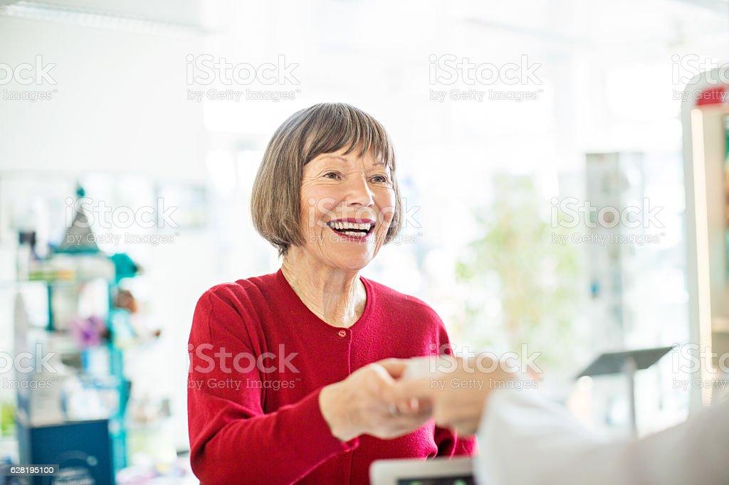 Female customer taking medicine from pharmacist stock photo