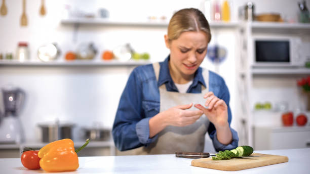 Female cut finger while slicing cucumber, accident in kitchen, household injury stock photo