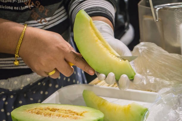 Female cutting Green Melon prepare to eat in Market Fresh Food Concept stock photo