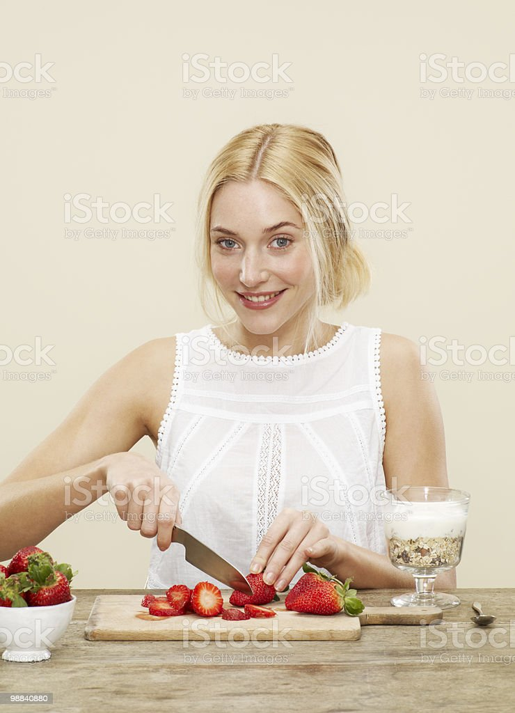 female cutting up strawberries for her breakfast royalty-free stock photo