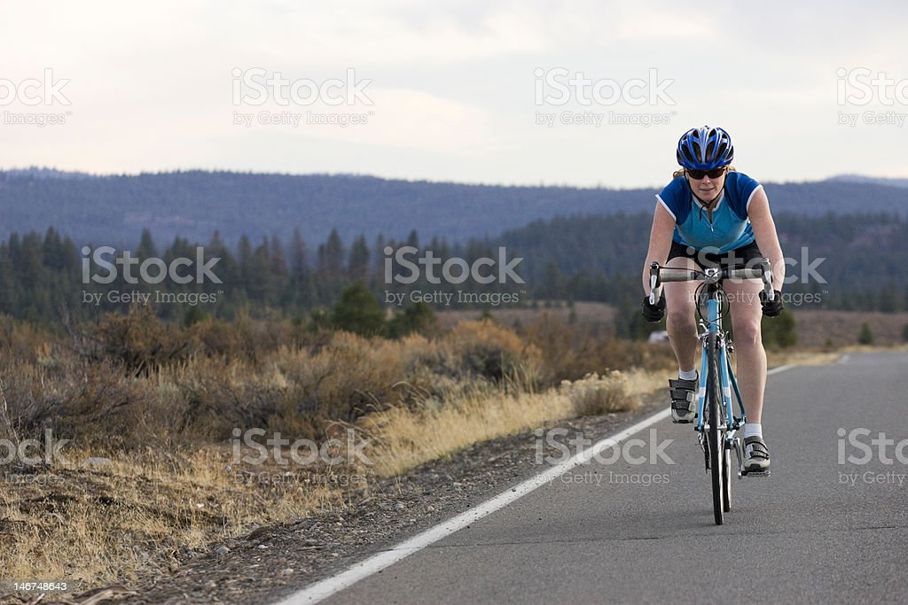female cycling on a flat road royalty-free stock photo