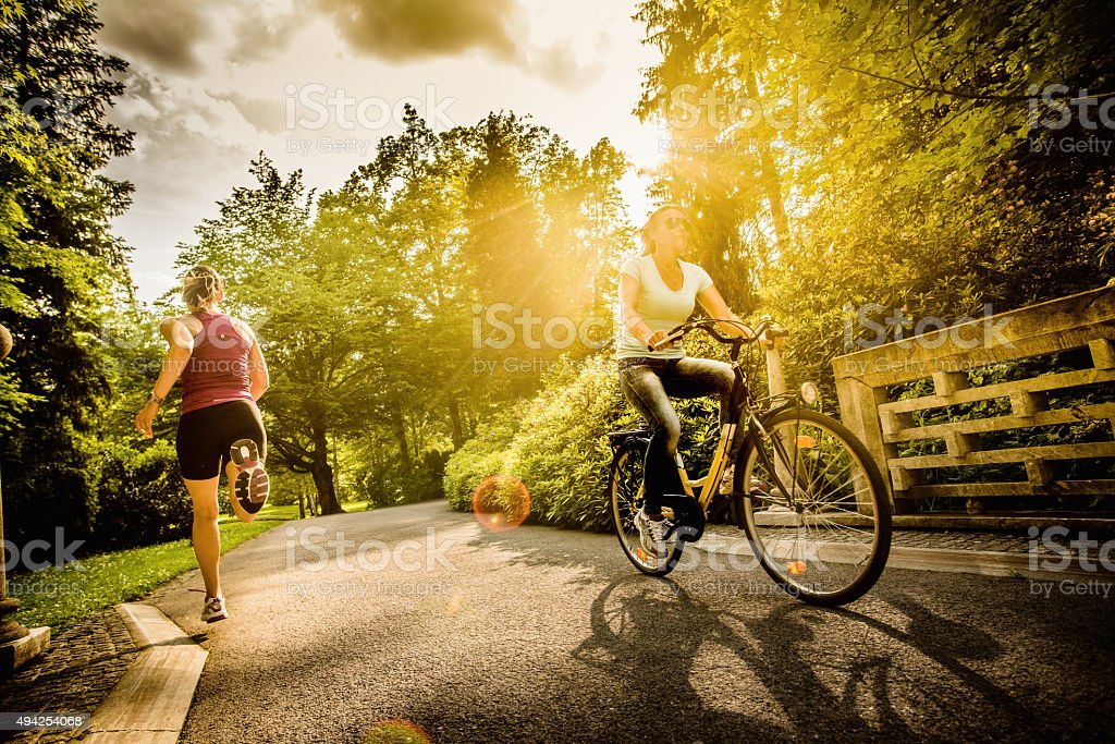 Female Cyclist and Jogger in a Park stock photo