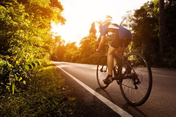 weibliche radfahrer radfahren bin den weg in die wälder und berge - fahrradwege stock-fotos und bilder