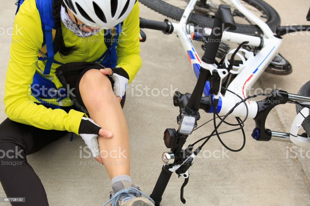 female cyclist getting injured while falling from mountain bike on road stock photo