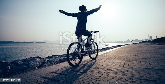 Female cyclist hands free cycling riding bike with arms outstretched in the coasts sunriseFemale cyclist hands free cycling riding bike with arms outstretched in the coasts sunrise Female cyclist hands free cycling riding bike with arms outstretched in the coasts sunrise