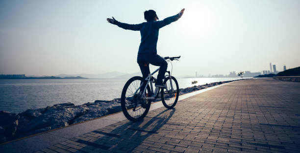 Female cyclist hands free cycling riding bike with arms outstretched in the coasts sunrise stock photo