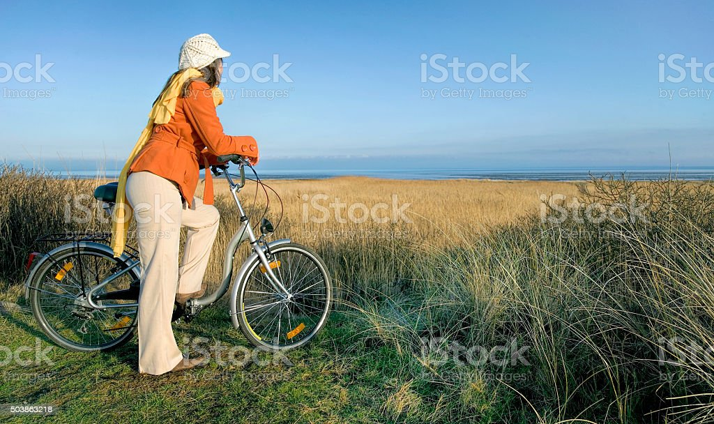 Female cyclist in winter clothes resting at coast stock photo