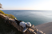 istock Female cyclist relaxes on rock wall above the sea 1142180485