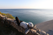 istock Female cyclist relaxes on rock wall above the sea 1142180491