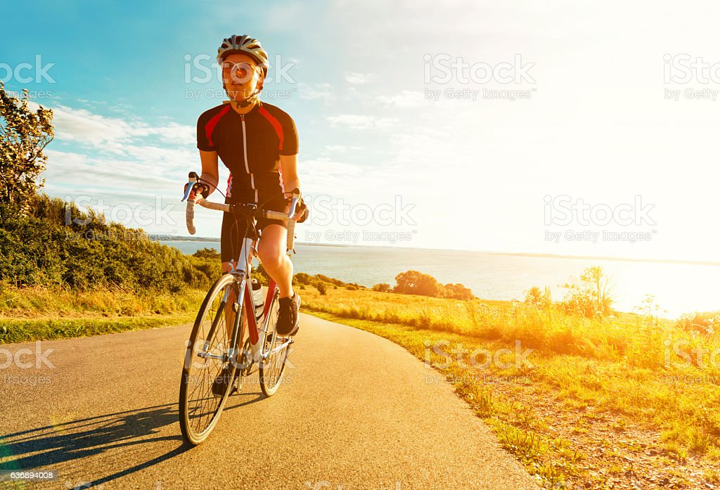 Female cyclist rides bike up a steep hill at sunset - foto stock