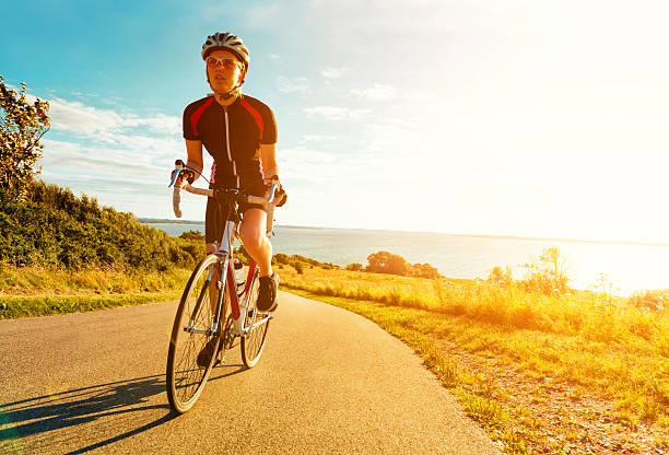 Female cyclist rides bike up a steep hill at sunset - foto de acervo