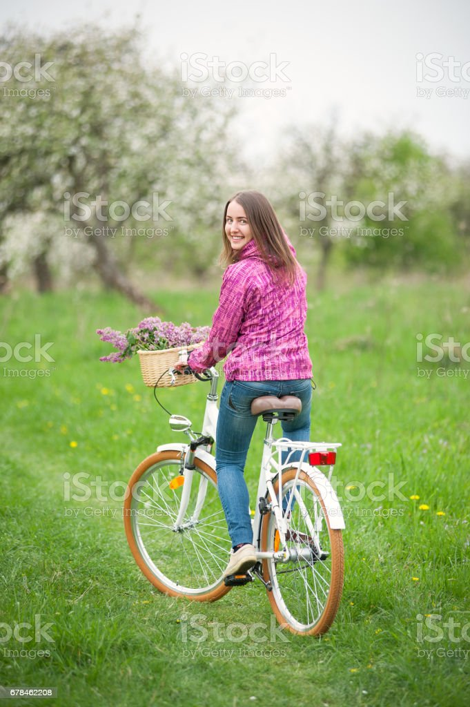 Female cyclist riding a vintage white bicycle in spring garden royalty-free stock photo