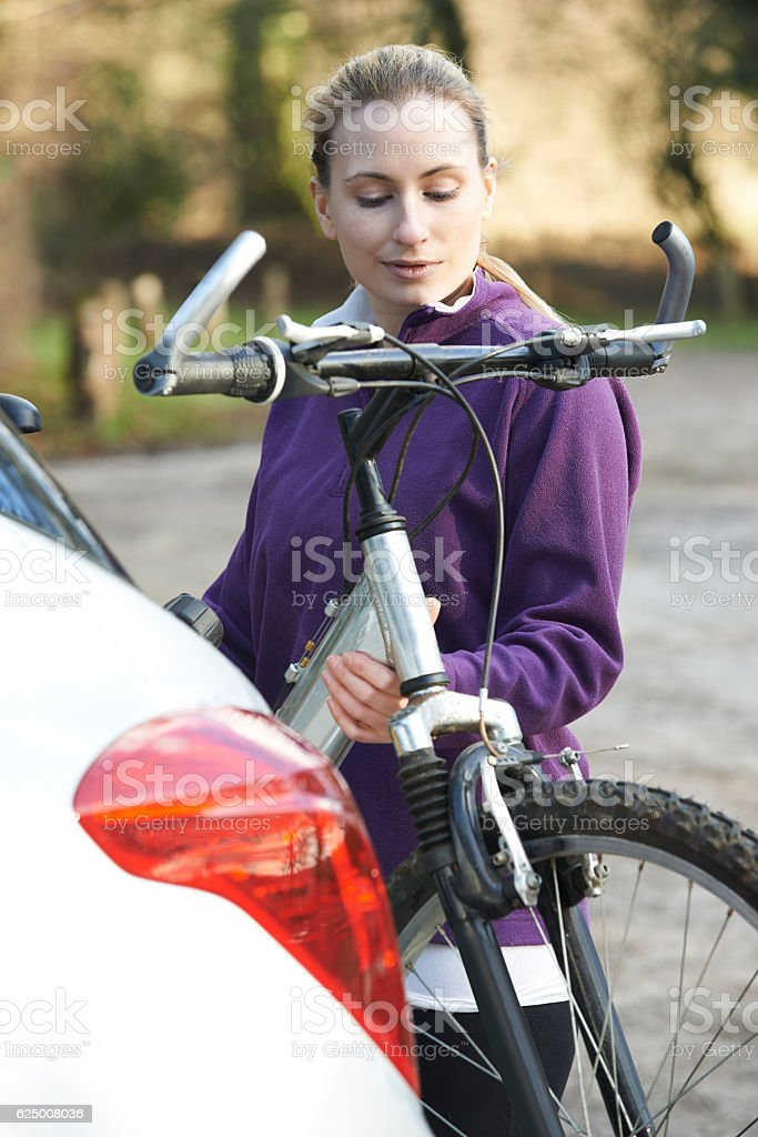 Female Cyclist Taking Mountain Bike From Rack On Car stock photo