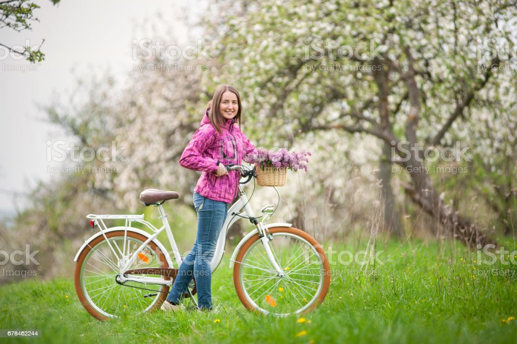 Female cyclist with vintage white bicycle in spring garden royalty-free stock photo