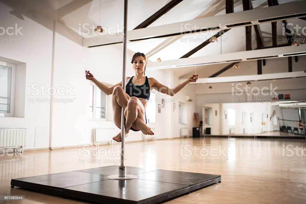 Female dancer doing teddy Buddha on a dancing pole. stock photo