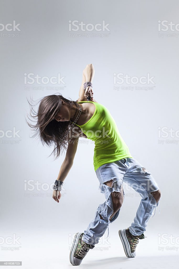 Female dancer with green tank top and torn jeans stock photo