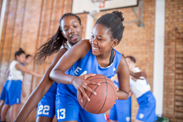 Female defending basketball from opponent Smiling female defending basketball from opponent. Teenage girls are playing match in court. They are in sports uniform. basketball sport stock pictures, royalty-free photos & images