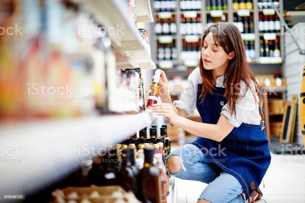 Weibliche Deli Besitzer arrangieren Flasche Salatsoße auf Regal im Laden – Foto